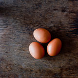 Three organic eggs on rural tabletop. Closeup of two organic eggs on a brown rural table top Stock Photos