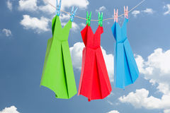 Three Origami paper dresses (green, red, blue) hanging on a clothes line in front of the blue summer sky Royalty Free Stock Images