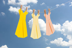 Three Origami paper dresses (pastel colors) hanging on a clothes line in front of the blue summer sky Royalty Free Stock Image