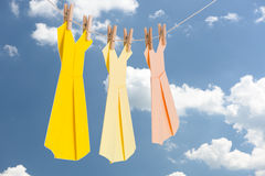 Three Origami paper dresses (pastel colors) hanging on a clothes line in front of the blue summer sky Royalty Free Stock Images