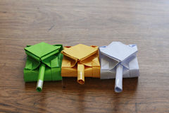 Three origami tanks on a wooden table top. Royalty Free Stock Images