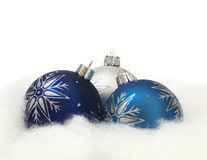 Three Ornaments in the Snow. Three Christmas ornaments nestled in cottony snow Stock Image
