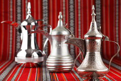 Three ornate Dallah pots are placed on traditional red fabric from the Middle East Stock Photo