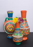 Three ornate pottery vases with two yellow and violet flower Royalty Free Stock Photo