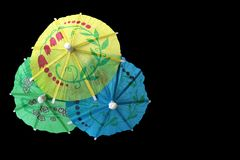 Three overlapping colorful paper cocktail umbrellas on black background. Three overlapping colorful paper cocktail umbrellas isolated on black background royalty free stock image