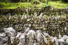 Three overlapping stone grunge walls with lichens and green vegetation in the park. Overlay stone walls texture background stock image