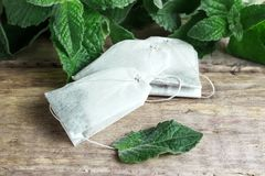 Three packets of tea on a mint background on a wooden background Stock Photos