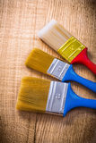Three paint brushes on wooden board construction Stock Images