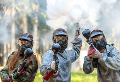 Three paintball players with guns and smoke grenade aiming Royalty Free Stock Photo