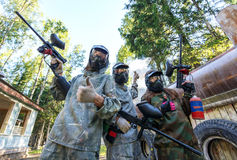 Three paintball players with smoke grenade posing in masks Stock Photo