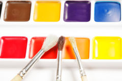 Three paintbrushes on box of dry aquarelle. Closeup stock photos