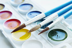 Three paintbrushes and set of various watercolo Stock Photos