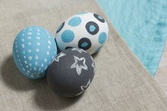 Three painted boiled eggs on a gray and turquoise napkin. Easter eggs with various patterns are painted with two paints: turquoise and gray Stock Photos