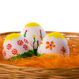 Three painted colorful Easter eggs in a basket Royalty Free Stock Image