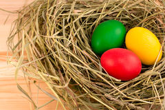 Three painted Easter eggs on the hay. Three painted in green, red, yellow Easter eggs on the hay Stock Photo