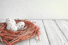 Three eggs with red spots in a hay nest. Easter Holiday. Three painted eggs with red spots in a hay nest. Easter Holiday royalty free stock photography