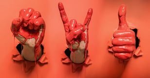 Three painted hands with different gestures. Are coming out from wall stock photos