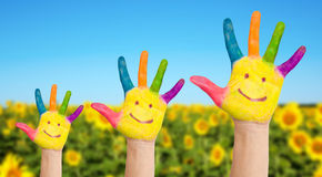 Three painted hands of family on sunflowers field Stock Photography
