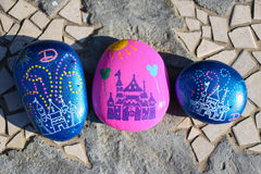 Three painted rocks resembling the castle at Disneyland. Three painted rocks on a garden bench.  Two are painted vivid blue and one is bright pink.  All have the Stock Image