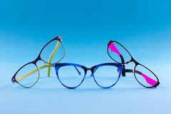 Three pair of lasses on the blue backgraund. Three pair of glasses different forms of colored spectacles on a blue background royalty free stock image