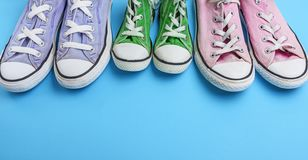 Three pair of old worn textile sneakers on a blue background stock images