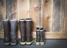 Three pair of rubber boots. Large and small brown rubber boots sitting next to a wooden barn door Stock Photo