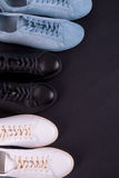 Three pair of sneakers on black background. Black, white and blue shoe. Top view. Copy space. Royalty Free Stock Photo