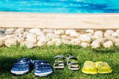 Three pairs of beach shoes near swimming pool Royalty Free Stock Image