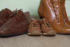 Three pairs brown of shoes on the floor after a wa. Family footwear on the floor after a walk Royalty Free Stock Image
