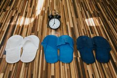 Three pairs of colored Slippers and an alarm clock. Bedtime royalty free stock photography