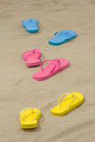 Three pairs of colorful flip flops on white sand Royalty Free Stock Image