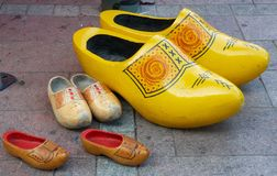 Three pairs of different size clogs. On pavement Royalty Free Stock Photo