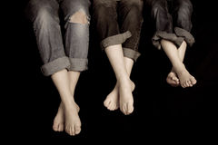 Three Pairs of feet. In  jeans rolled up on a black background. One pair of jeans ripped at the knee's Stock Images