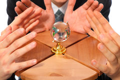 Three pairs hands and glass globe on stool Royalty Free Stock Photo