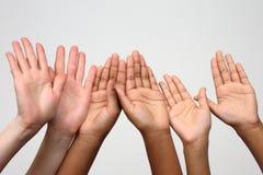 Three pairs of hands raised up