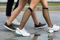 Three pairs of slim fit young girls legs in different sport shoes walking fast along the concrete road.Busy city lifestyle. Three pairs of slim fit young girls Stock Photos