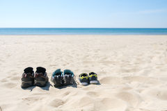 Three pairs of sneakers are on the sand. The concept of the weekend.  Stock Image