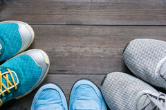 Three pairs of sport sneakers closeup on dark wooden background Royalty Free Stock Photography