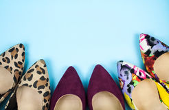 Three pairs of stiletto shoes in different colors and patterns on light blue background. Royalty Free Stock Image