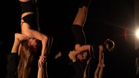 Three pairs take turns performing an acro yoga trick. Men and women in sportswear are engaged in acro yoga, the girls stand upside down on the feet of men stock footage
