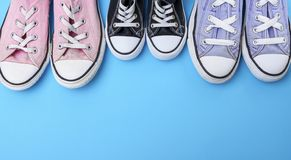 Three pairs of textile worn shoes on a blue background stock images