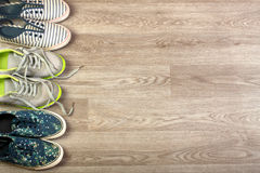 Three pairs of various running shoes laid on a wooden floor background. Royalty Free Stock Photography