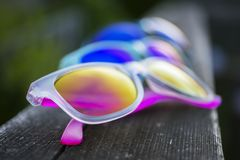 Three pairs of vibrant sunglasses in multiple colors. Lined on a wooden summer deck railing, fashion and uv eye protection concept Stock Images