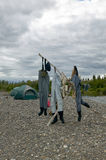Three pairs of waders drying on a river bank. In the Kipchuck River in Alaska on a fly fishing trip with tents in the background Royalty Free Stock Image