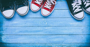 Three pairs of wearing sneakers on a blue wooden surface, top vi. Ew, an empty space, vintage toning Royalty Free Stock Photo