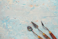 Three palette knifes on artist canvas with oil paint Stock Photo