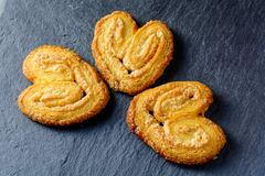 Three palmier cookies on a black board stock photo