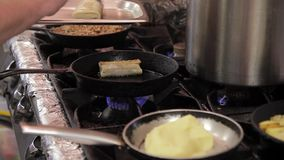 Three pans on stove in industrial kitchen variety dishes in restaurant stock footage
