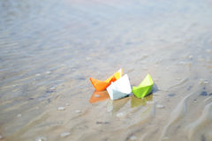 Three paper boats blue, green and orange water. Three paper boats running on water Royalty Free Stock Photography
