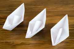 Three paper boats on a wooden table Stock Photos